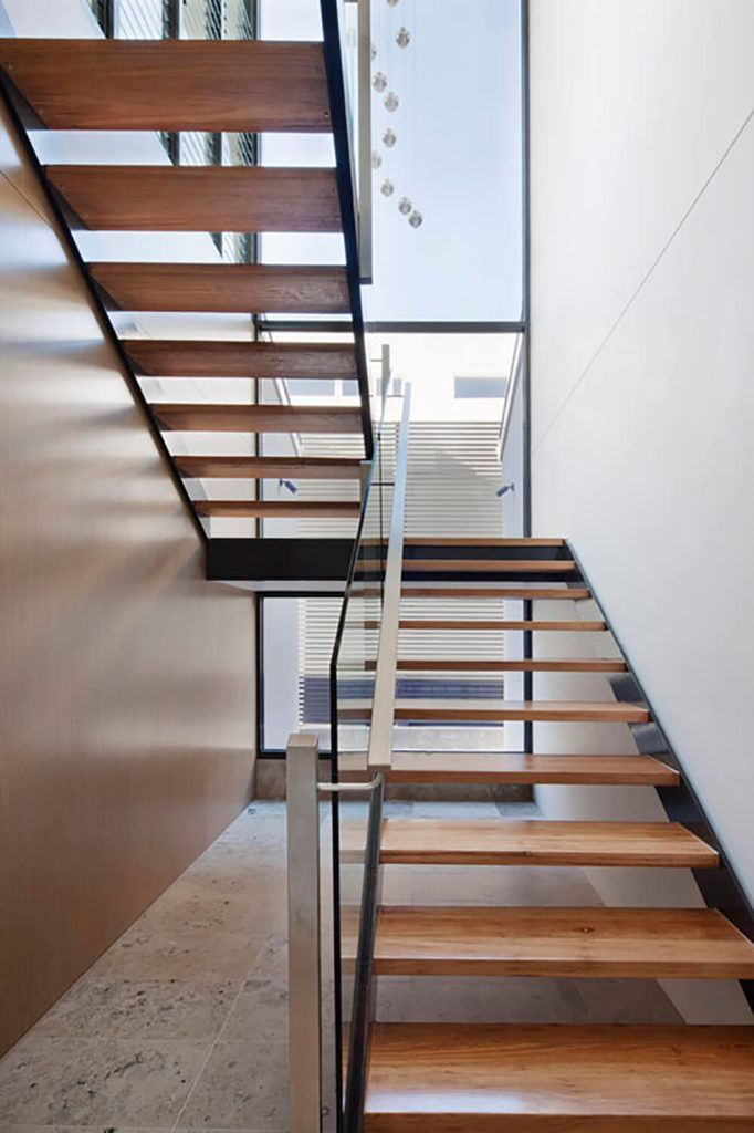 The designers wanted to create a functional stairwell up the to second level as well as a space that would serve the purpose of bringing more light into the home. Thus, this open concept stairwell was designed to achieve this goal. The open stairs allows for optimal amounts of light to reach into the house through the large windows.