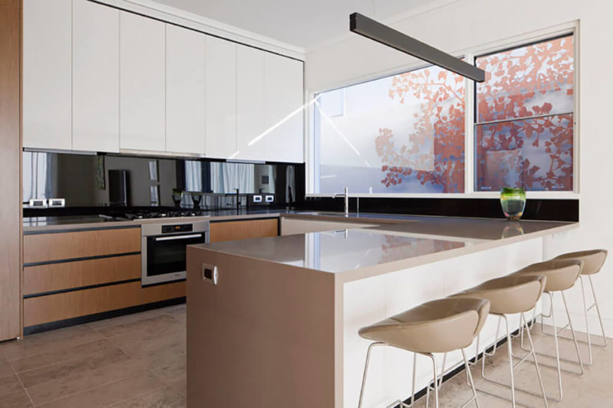 The original kitchen, which opens to the living room, was small and inefficient. The owners wanted the space expanded and updated. Adding sleek cabinets and counters, as well as a more streamlined workflow adds to the modern design of the space. The natural wood of the bottom cabinets brings warmth to the reflective surfaces prevalent in the design.