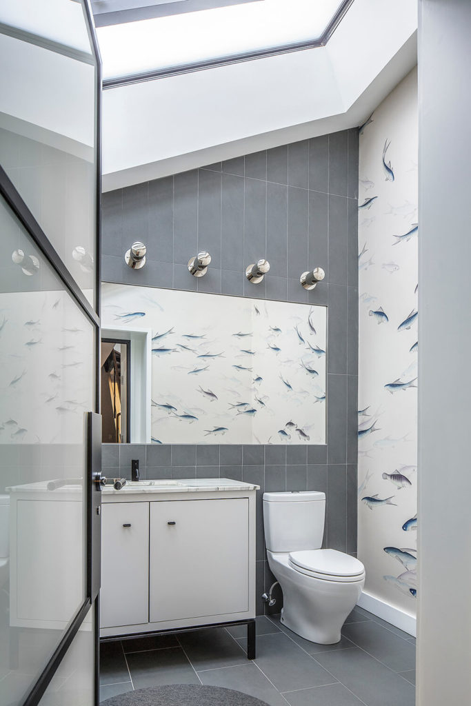 Grey tile that is consistent with that which was found in the entryway covers this bathroom. Where the tile is absent, painted fish accent the white walls. White marble makes up the countertop.