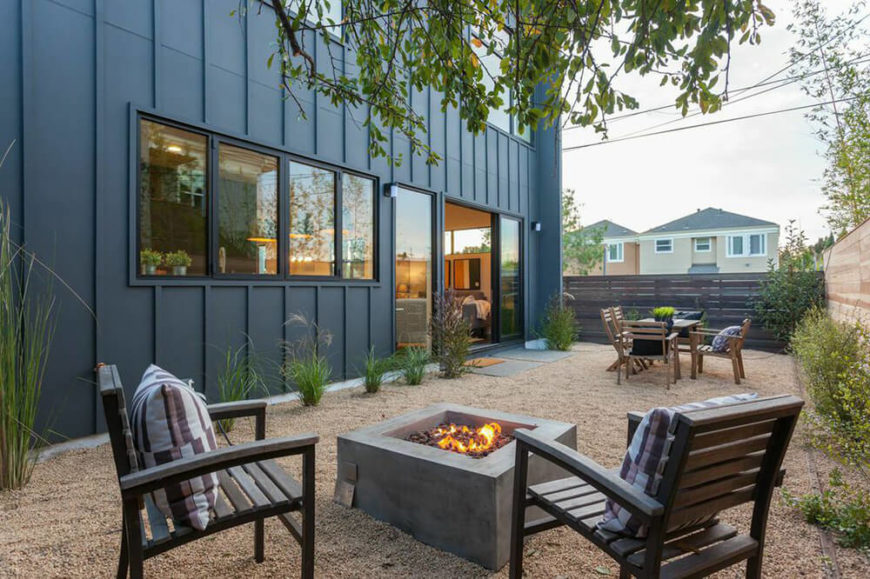 Pea gravel covers the ground in this outdoor lounging area. There is a square fireplace with chairs set around it, as well as an outdoor dining table. Various shrubs and green grasses accent the space with color.