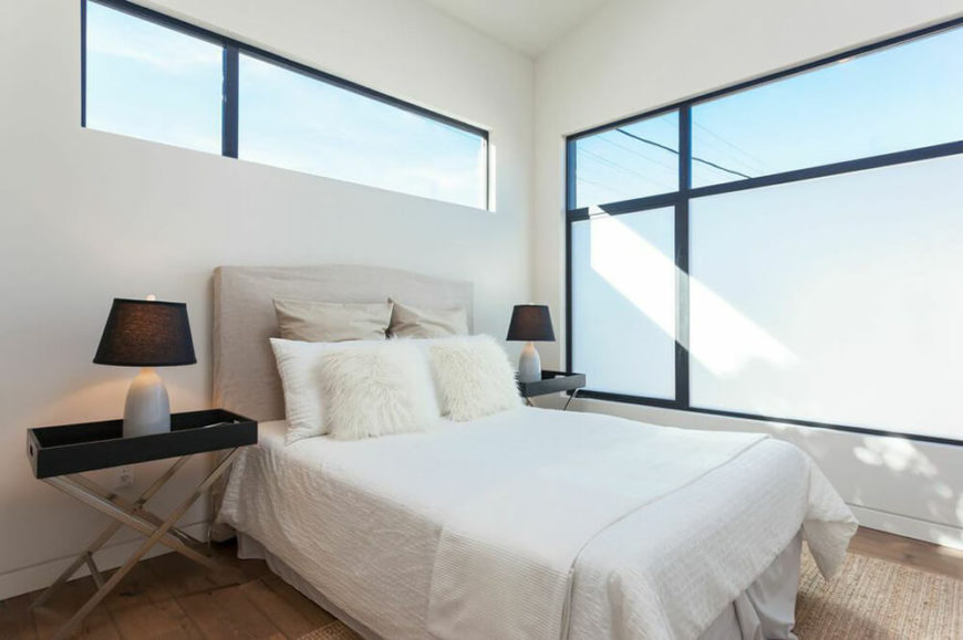 This modest bedroom features large windows that let natural light completely illuminate the room. The windows have a light frost on the lower sections, allowing for the bedroom to still have privacy. On either side of the bed, there are symmetrical side tables with matching lamps.