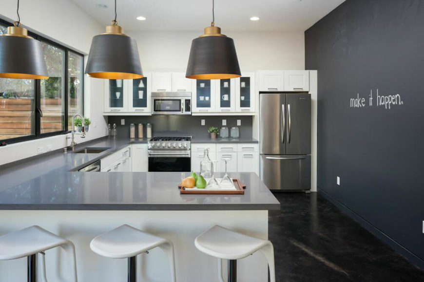 The kitchen in this home is located on the lower level. There is a large U-shaped counter with an eat-in extension, with large lamps hanging overhead. The appliances are chrome and match the countertops.