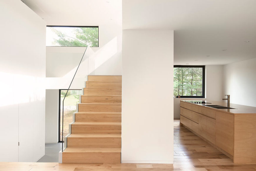 This image gives us a wonderful idea of how this house has been designed to be open and free flowing. The kitchen is spacious, and features a large island containing the sink and stove. From this one angle, we also get a view of the stairs leading up to the top level, and can even see the entryway as well.