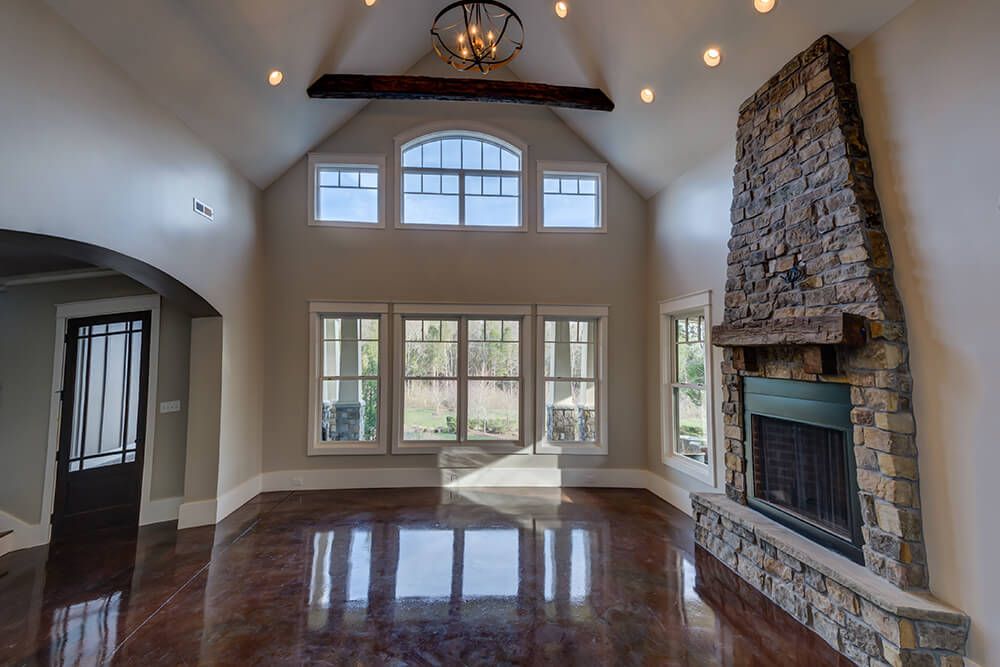 A classy home featuring sparkling tiles flooring surrounded by light gray walls and under the high vaulted ceiling.