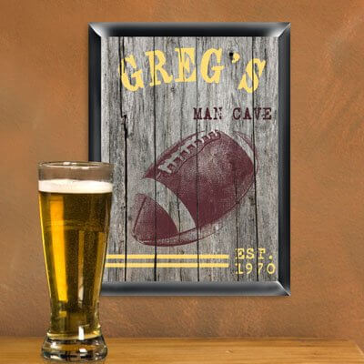 "We love the idea of hanging up cheeky ""man cave"" signs in the man cave, a knowing wink to the boys' room history of the space. It's always great when wall decorations combine a couple passions. In this case, we see a football themed sign done up in antique textures for a rustic, old fashioned appearance. This one can be personalized with up to 15 characters at the top and 30 characters below."