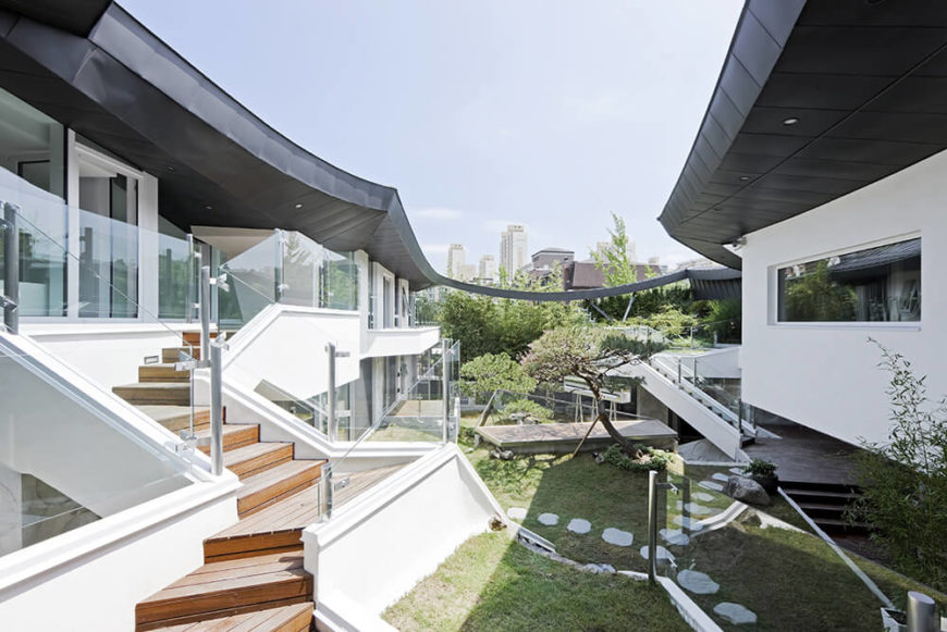 Viewing across the length of the courtyard, we can take in the breathtaking layered appearance of the design, mixing glass, steel, grass, and white walls beneath a subtly enveloping roof in black.