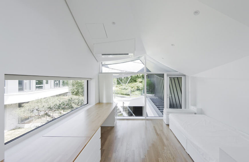 In one of the upper level bedrooms, we see a lengthy built-in desk with sleek white cabinetry, across from the bed set against the wall. The curved roof lines are apparent here, and the exterior view is afforded by perfectly shaped windows reaching floor to ceiling.