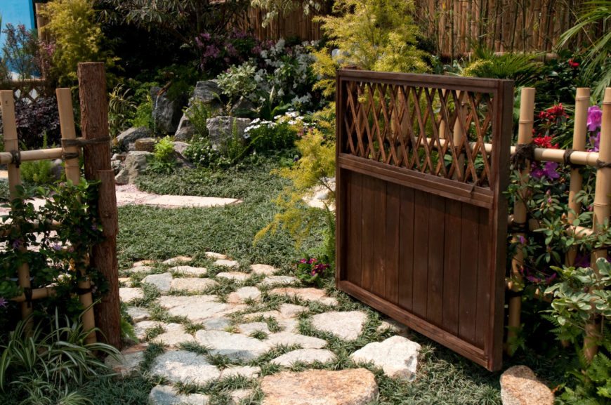 """This decorative """"picket"""" bamboo is attached to a dark stained solid wood gate and terminal posts, providing access to the lush back garden via a slightly overgrown flagstone pathway."""