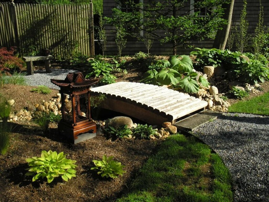 A beautiful Zen garden with a tall bamboo fence. Unlike most bamboo fences, which have cut-off tops, this fence has pointed tops, similar to more western style fences.