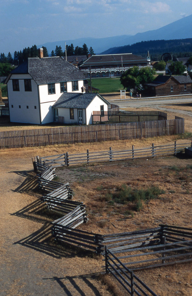 An old farmhouse with a sturdy split rail fence meant to corral horses. The aged fence fits perfectly into the Old West atmosphere of the farmhouse and surrounding prope