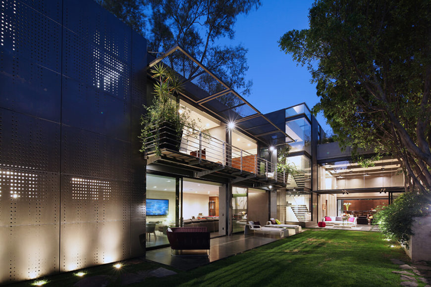 The sprawling layout features full height openings and glass panels toward the garden side on nearly every room, with a shaded section to the left obscured by perforated panels. The aluminum louvers make for perfect shading during the day time.