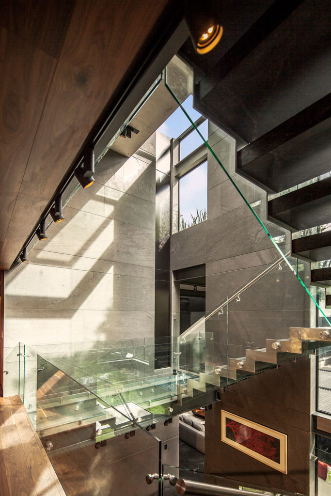 In the tall central volume, we see the immaculate steel and glass staircase criss-crossing the entire space. The contrast between sleek modern materials and stone structure emphasizes the striking visual nature of the home itself.