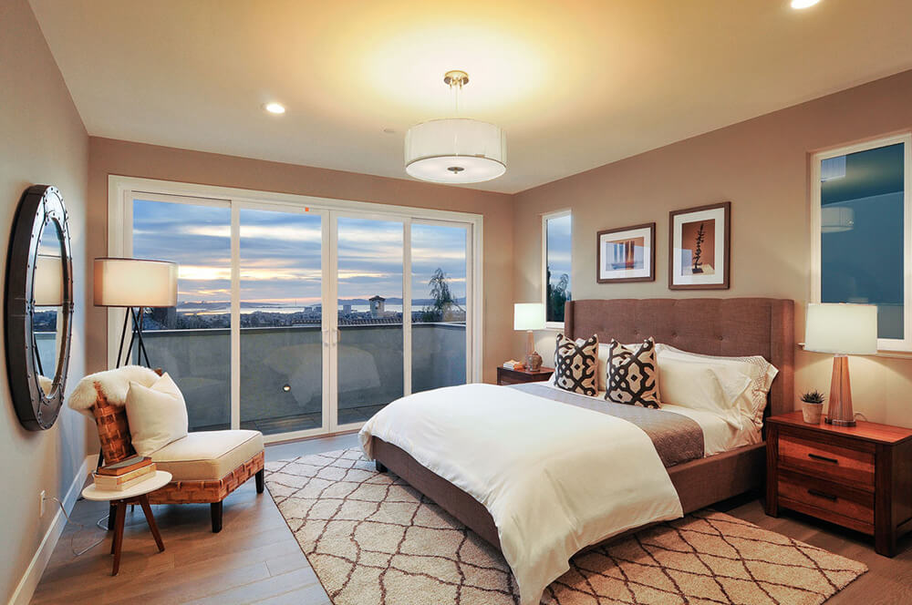 Classy medium-sized master bedroom with a hardwood flooring topped by a rug. There's a doorway leading to the room's terrace area.
