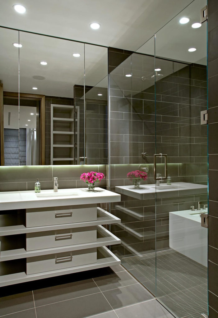 This bathroom, attached to the guest bedroom, features a large tub and shower in the same glass enclosed space. A large vanity with unique shelving and a creative design, offers up plenty of space for guests to prepare for the day.