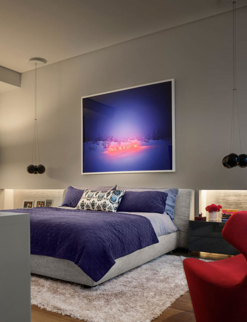 The bedroom features bold colors to reflect the artwork chosen for the focal point of the room. Rich blues and bold reds set this room apart from the rest of the house while the neutral walls allows these colors pop even more.
