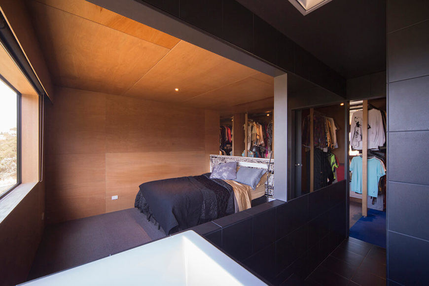 The bedroom, on the upper level, features a unique open en suite design, with a massive walk in closet area seen in the background. The sleeping area itself is spartan, surrounded by the rich tones of natural wood.