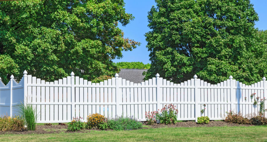 A lovely white vinyl picket fence with a delicate scalloped silhouette. A small planting bed follows the fence around the yard, adding color to the yard.