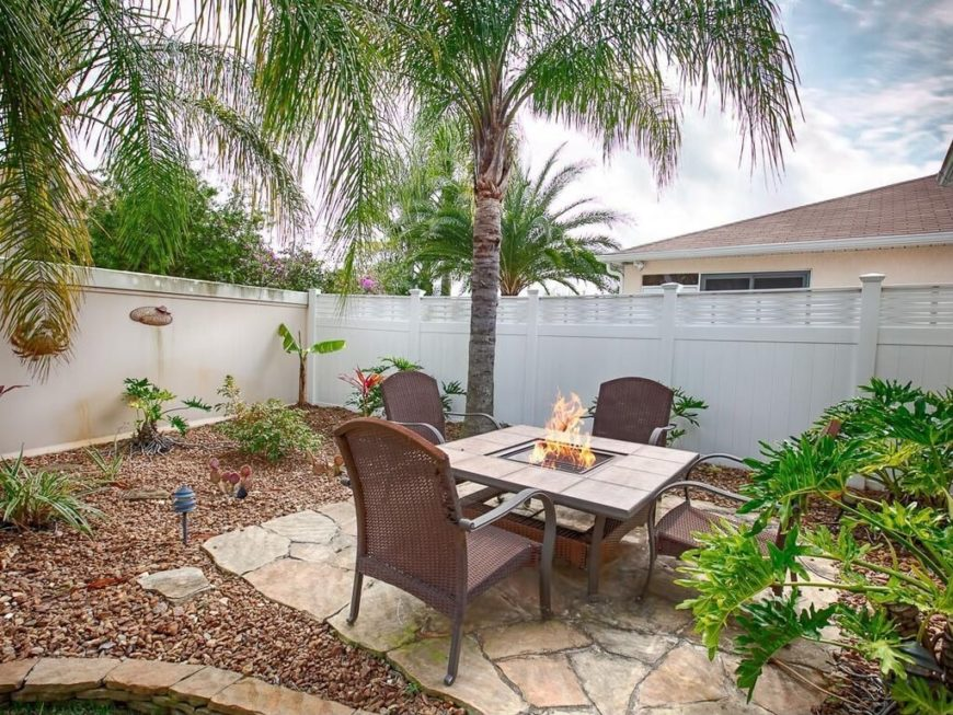 A simple vinyl privacy fence with a decorative border at the top that connects to a plaster fence. The result is a closed off, private backyard patio with exotic palm trees for shade.