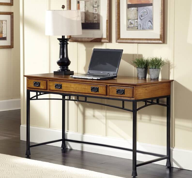 Note the familiar dark powder coated metal framing and slim, but recognizable arches spanning between the legs of this sleek and slim desk, perfectly meshing with the rich oak table top. The wood portion of the desk features a set of discreet drawers, perfect for a little bit of storage when you need it most.