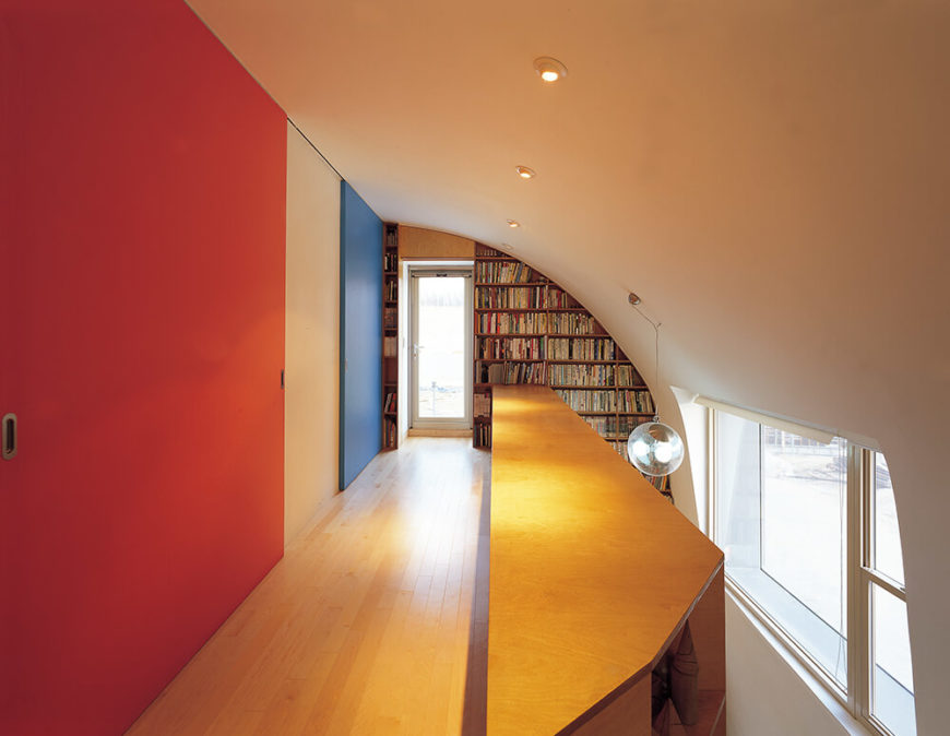 Turning the opposite direction, we see the singular hallway connecting the bedrooms on the upper floor, literally bookended by the library sized shelving wall at the far end.