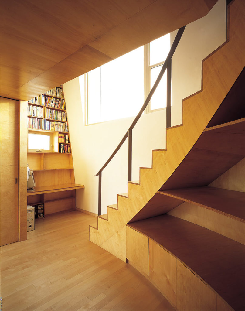 At the bottom of the lengthy staircase, we see much more of the sleek natural wood paneling, shelving, and hardwood flooring that informs the interior. Large windows allow natural light to spill throughout the home.
