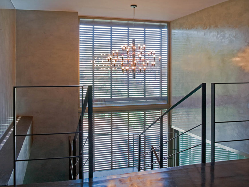 At the top of the stairs, we can appreciate the way the thin metal railings complement the open design, making for a clear visibility from one floor to the next. A unique chandelier hangs above this two story void.