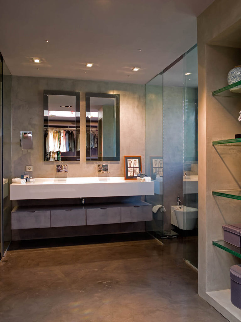 The master bathroom is awash in varied materials, with glass panels separating the water closet and walk-in showers from the main area, and a lengthy floating white vanity over grey storage cabinetry.
