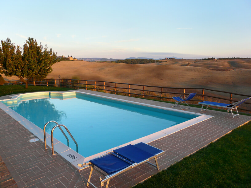 A simple post style fence separates a pool from the rolling hills. This style does not block much of the view.