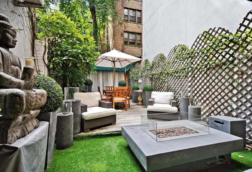 This backyard features an Asian style narrow patio bordered on one side with a decorative latticed fence. The top of the lattice panels are scalloped.