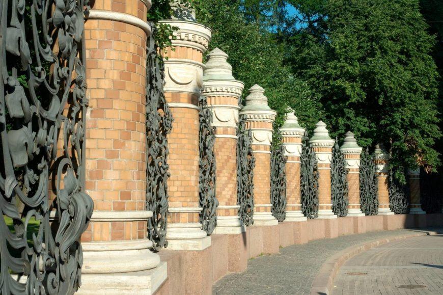 A very ornate wrought iron pattern between brick pillars.