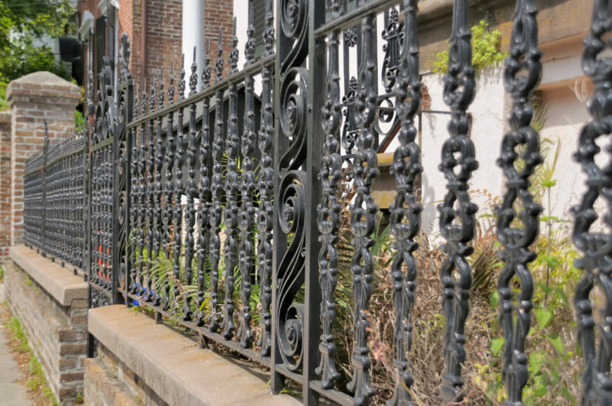An intricate design on a shorter wrought iron fence.