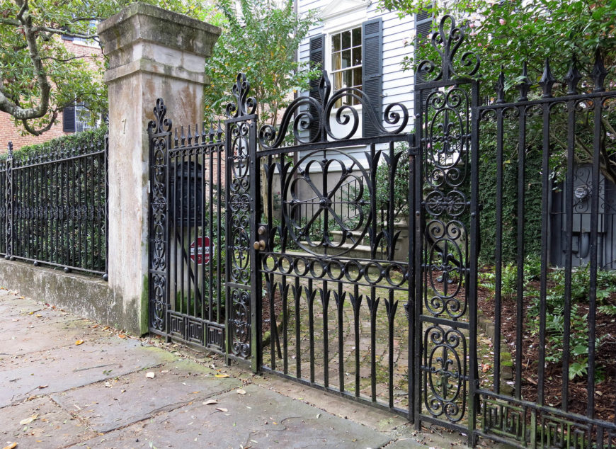 A tall intricate wrought iron fence with an ornate gate.
