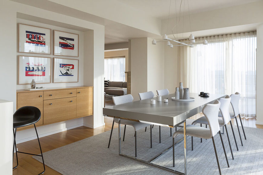 The dining room centers on a massive ultra-modern table with a sleek grey surface and stainless steel frame. Slim, minimalist chairs flank the table and emphasize a connection with the large area rug over hardwood flooring.