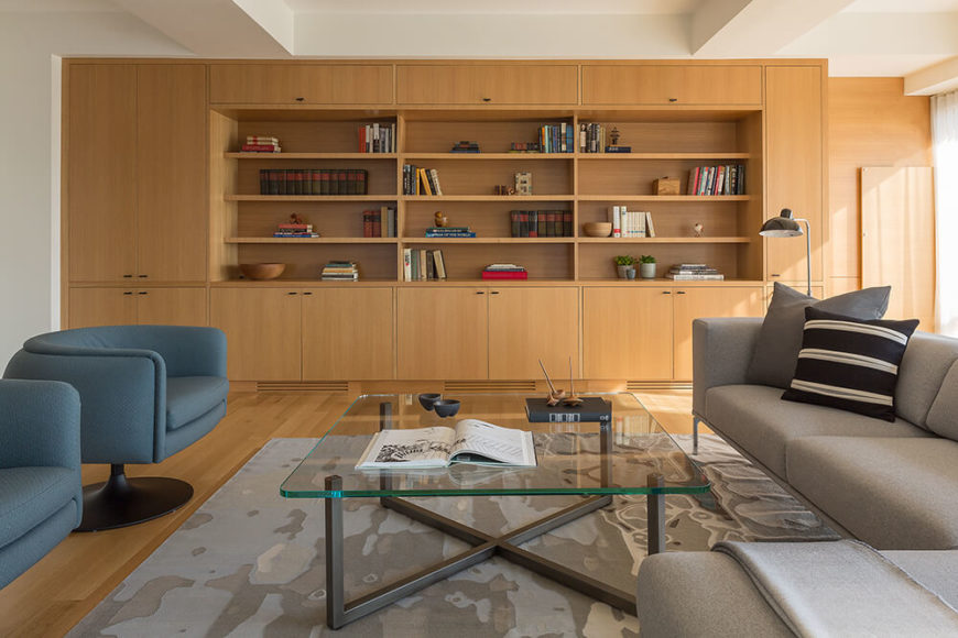 Here's a look at the rich wood paneling and matching hardwood flooring, an element that grants some warmth and contrast to the cool modern tone of the design. An abundance of discreet built-in shelving and cabinetry enhances the living room.