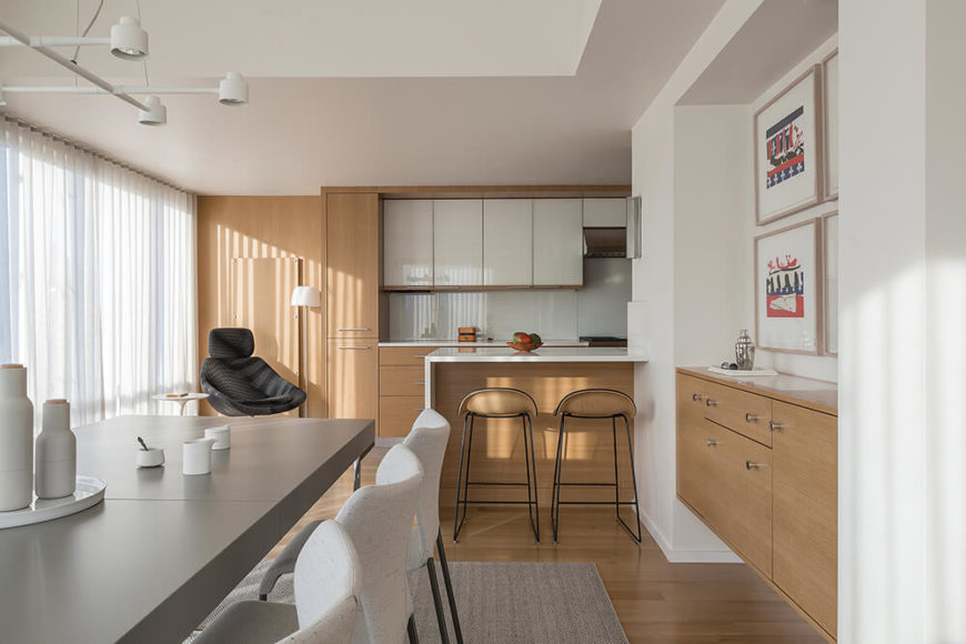 The open floor plan means that the kitchen opens right into the dining area. Glossy white cabinetry and countertops define this area as distinct from the remainder of the home, while the rich wood paneling and lower cupboards offer a connection.