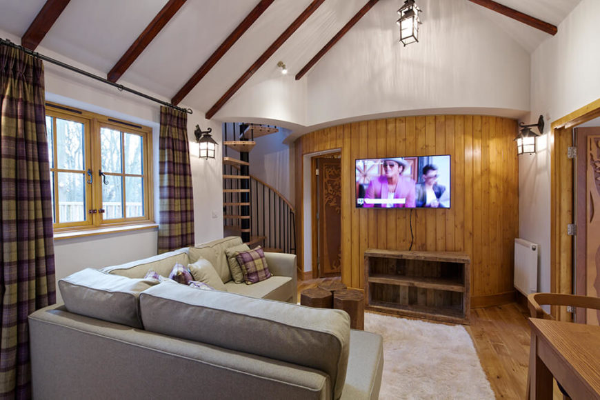 A spiral staircase leads back down to the main living area, where we can see the door to the bathroom and a large television.