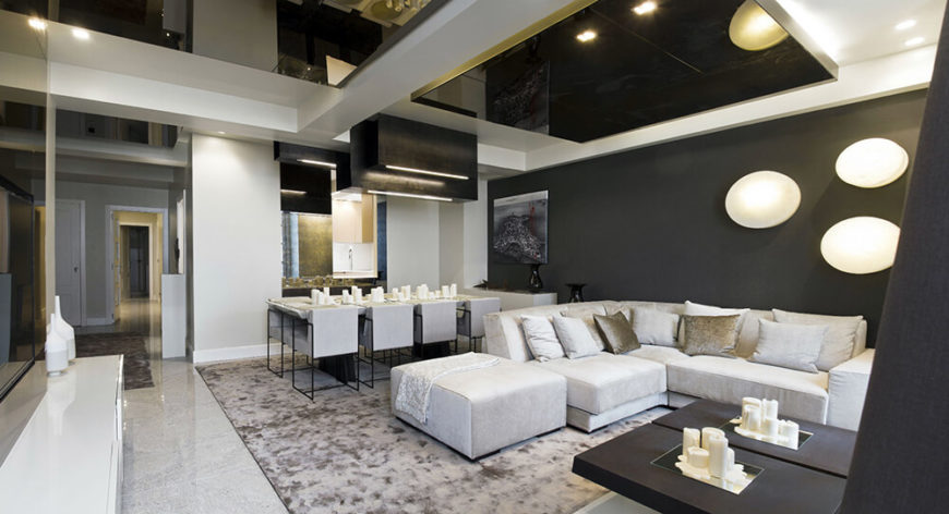 Here we see the vast open plan living and dining room, with sleek whites and greys warmed by subtle touches of vanilla. Sharp angles and high contrast design informs the look of the home.