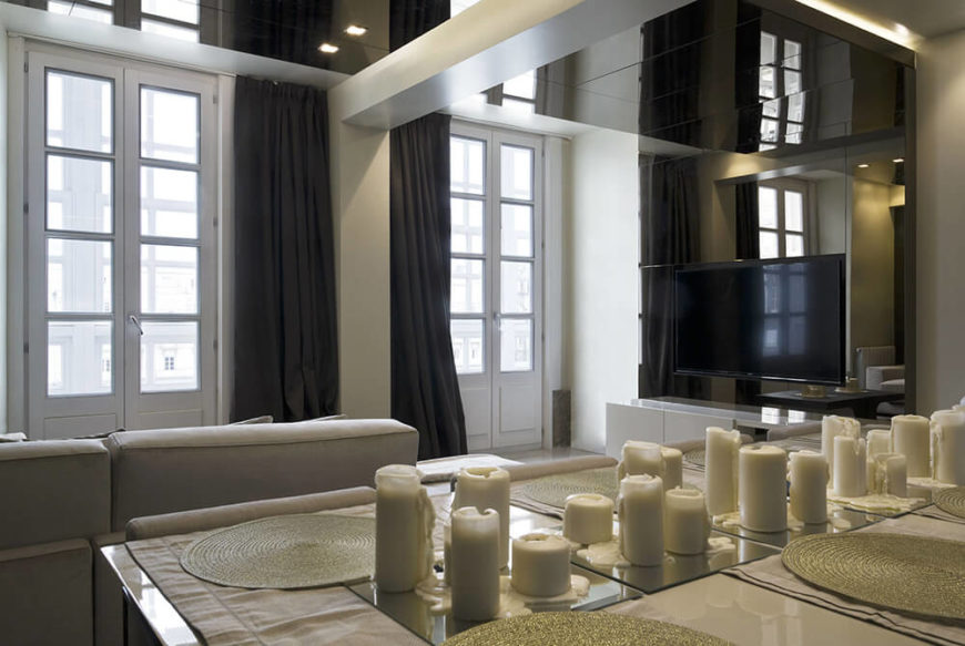 The home design makes use of sharply defined features, sleek surfaces, and high contrast colors to evoke a striking mood. The neutral whites and beige tones help unify the disparate elements.