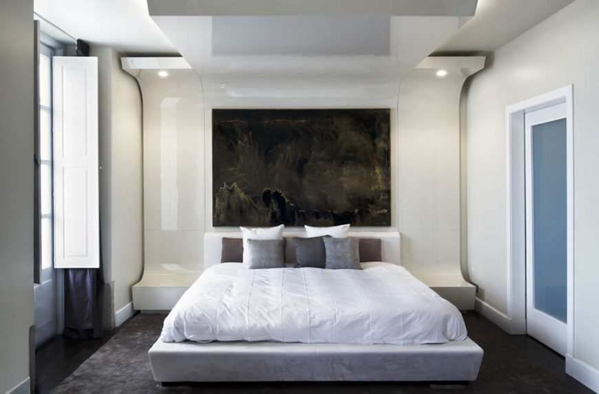 The primary bedroom features one of the most striking elements in the home, with a massive feature wall that curves into bedside tables as well as the ceiling above. This frames the bed in glossy, bold whites in direct contrast to the dark wood flooring.