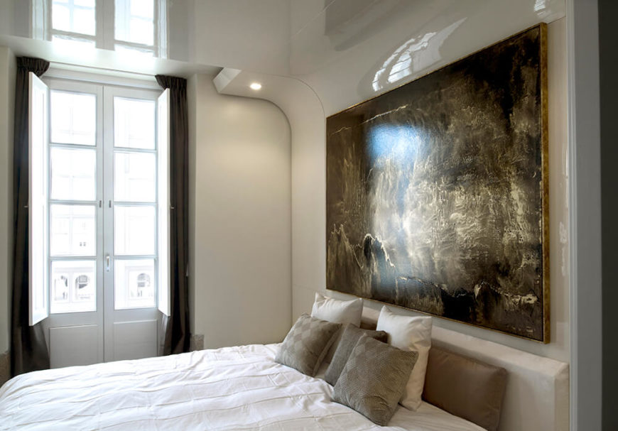 On the glossy feature wall, we see the large painting by Joaquín Torres and Rafael Llamazares. Subtle artwork like this brings a sense of lived-in history to modern designs.