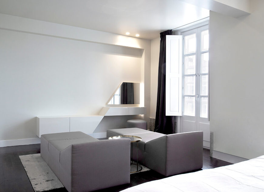On the opposite side of the massive bedroom, we see the sitting area. Comprising a pair of angular chaise lounges, this space also boasts a futuristic vanity and triangular mirror.