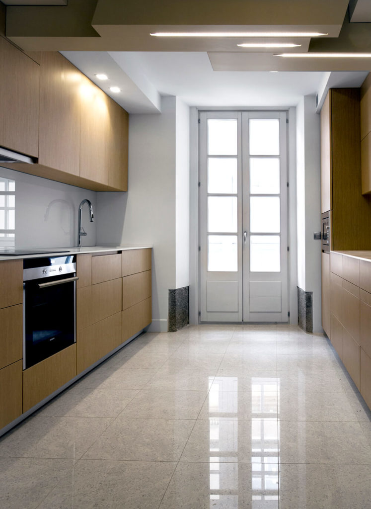 The kitchen brings a sense of warmth and timelessness with its sleek natural wood paneling, a great contrast to the cool look seen elsewhere in the home. Large format granite tile flooring anchors the space in luxurious elegance.