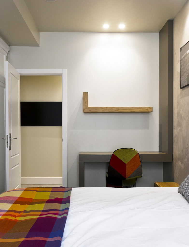 Here's a look at a childrens' bedroom in the home, differentiated from the primary bedroom by the bold use of rainbow colors. A writing desk is built-in to the wall in angular grey tones, with a similarly shaped natural wood floating shelf above.
