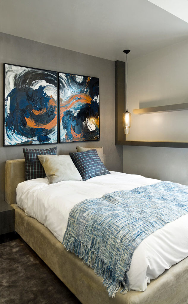 Here's a guest bedroom in the home, splitting the color difference between the previously featured rooms with a splash of subtle coloring, courtesy of accent pillows and artwork on the wall.
