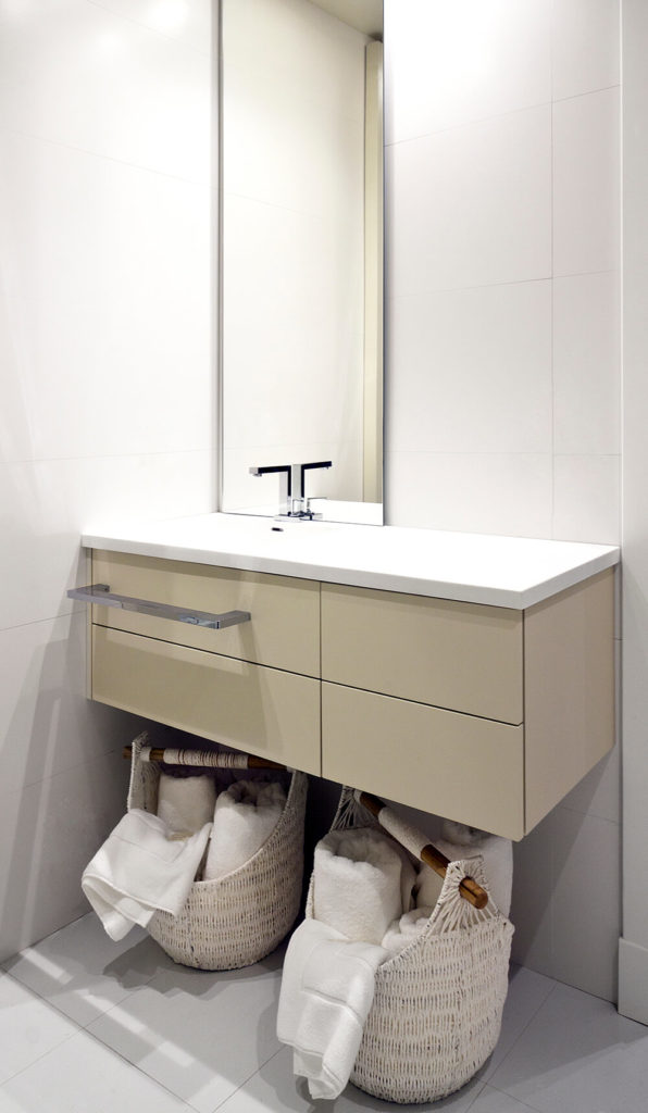 This bathroom features a floating vanity in beige and white, with a simple frameless mirror positioned along the pristine white wall above.