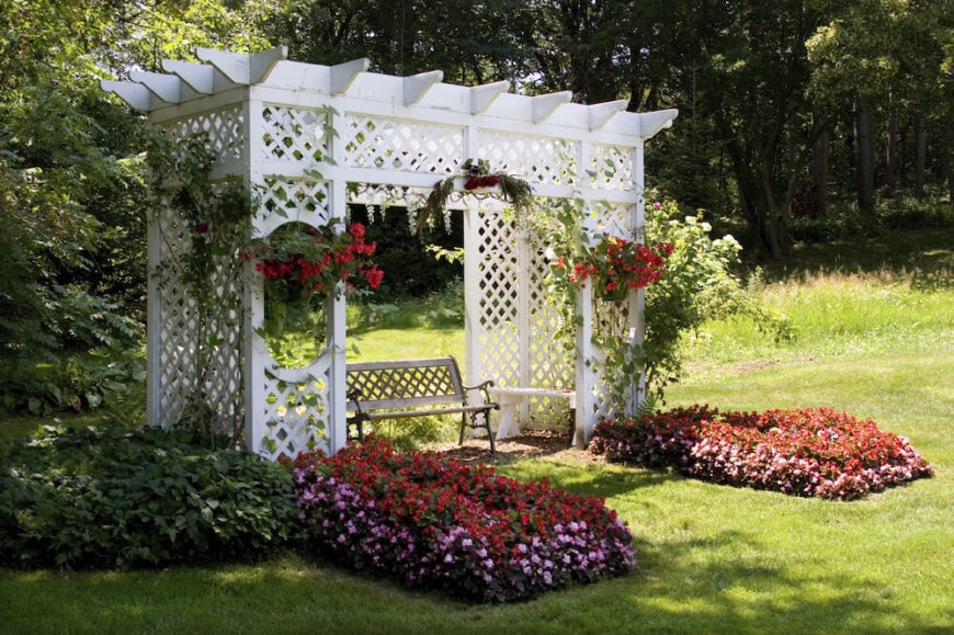 this white pergola is nestled above a small garden patio and bedecked with hanging baskets