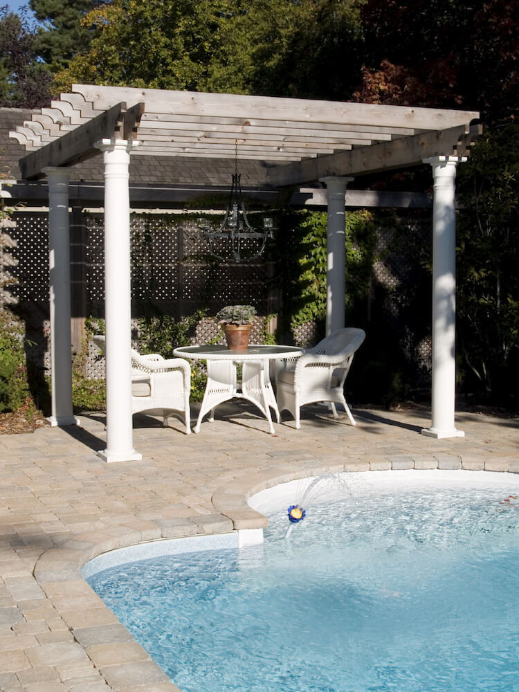 A poolside pergola above a small wicker dining set. The pergola doesn't provide a lot of shade, but is the perfect small, unobtrusive structure to hang a wrought iron chandelier.