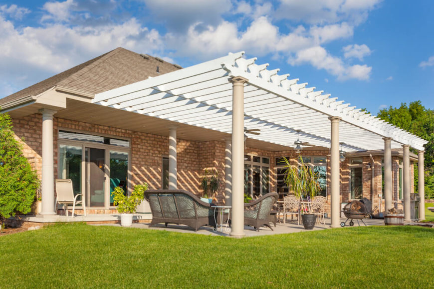 This large pergola is attached to the narrow back veranda and extends over a larger patio area. This pergola adds a bit of grandiose style to this patio, drawing the eye upwards.