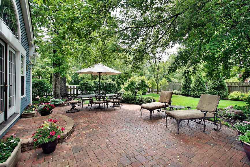 A lovely brick patio with a mosaic type layout. This patio is spacious, with plenty of space for two lounge chairs, a dining set with an umbrella, and lots of decorative containers of flowers. The patio is shaded by several mature trees, but looks out onto the yard.
