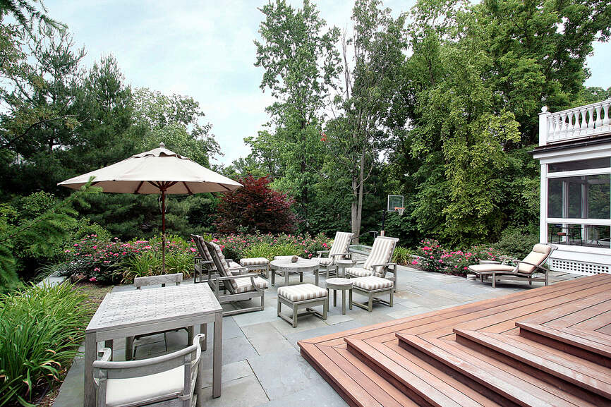 A large open patio tucked into a private garden. Steps lead down from the wooden deck. The outdoor patio complete with plenty of seating is overlooked by a balcony and screened-in sunroom.
